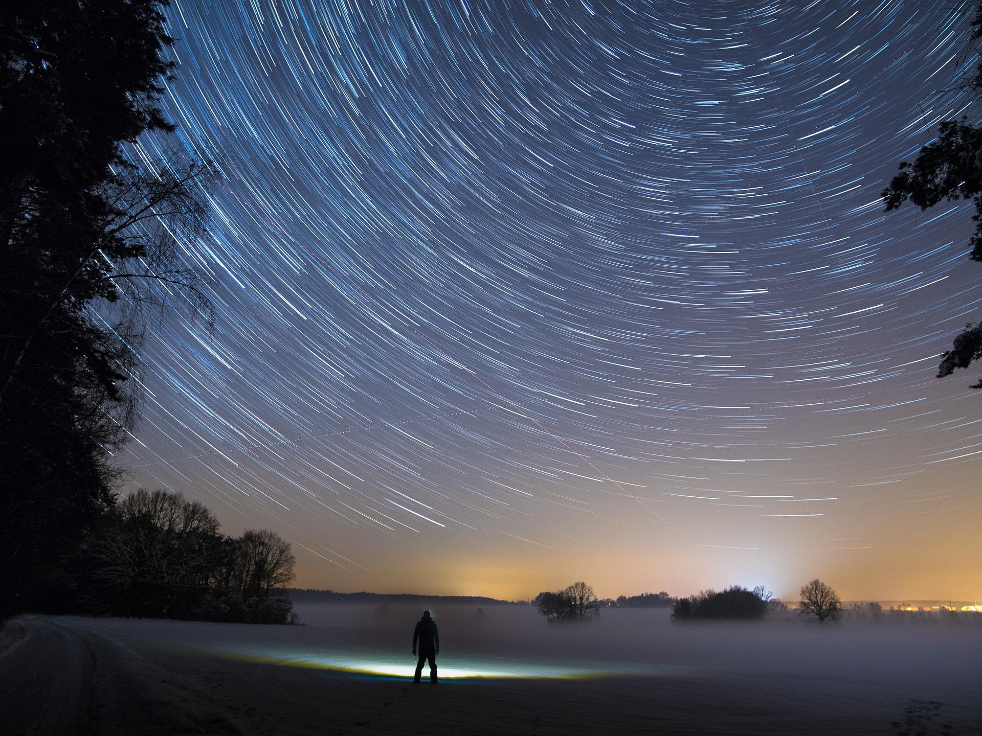 Homme seul dans un paysage enneigé de nuit. Vue sur le ciel étoilé en mouvement. Lumières à l'horizon.